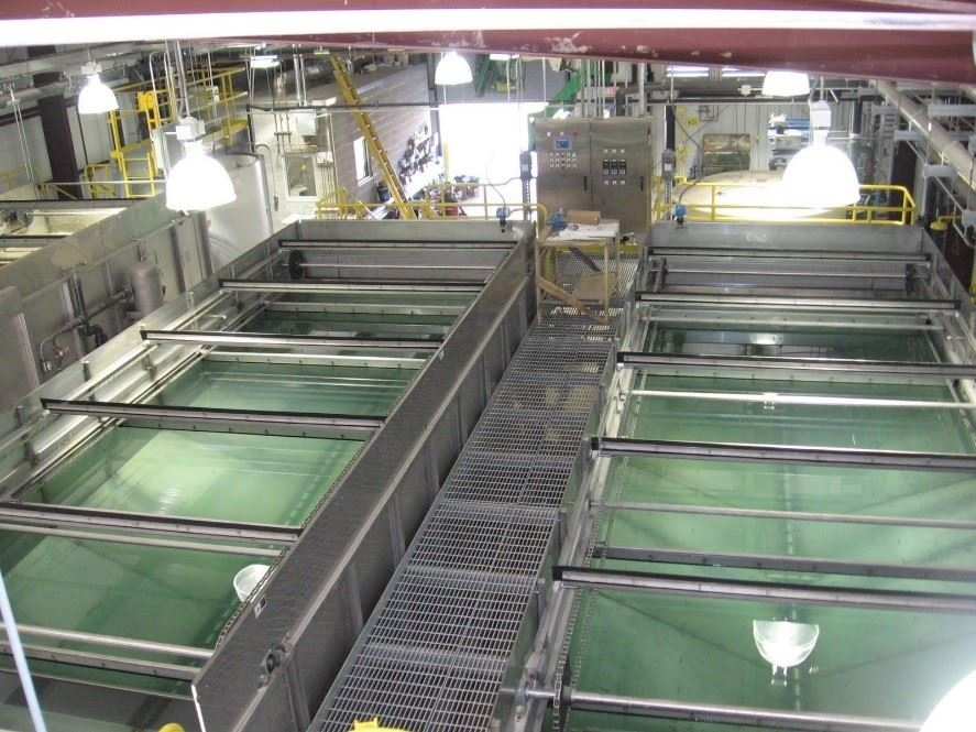 Large rectangular vats containing greenish-blue wastewater