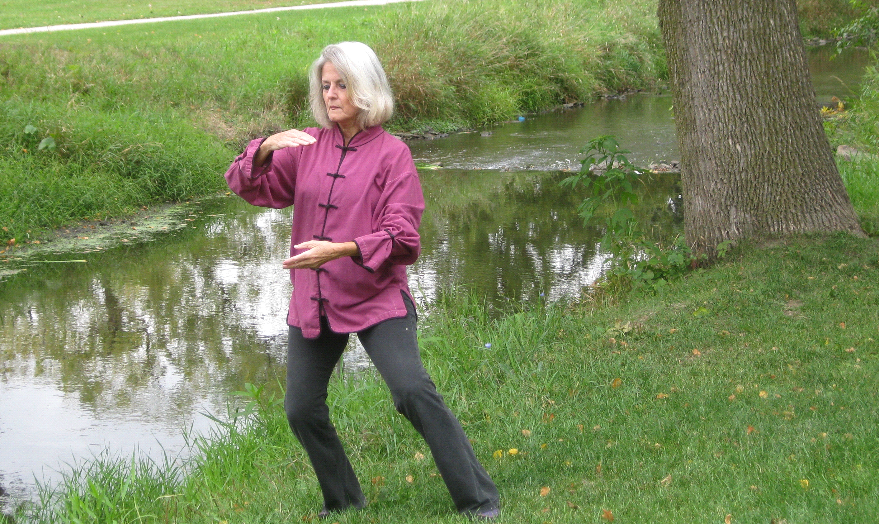 Tai Chi move by lady standing in grass along water edge.